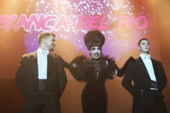 A photo of RuPaul's Drag Race queen Bianca del Rio flanked by two men on stage in Toronto