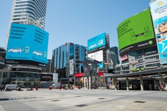 Public advisories on social distancing are displayed in Dundas Square in Toronto.