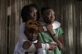A photo of Lupita Nyong'o clutching two children in the movie Us