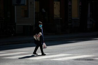 A person walks across the street in Toronto during the COVID-19 pandemic