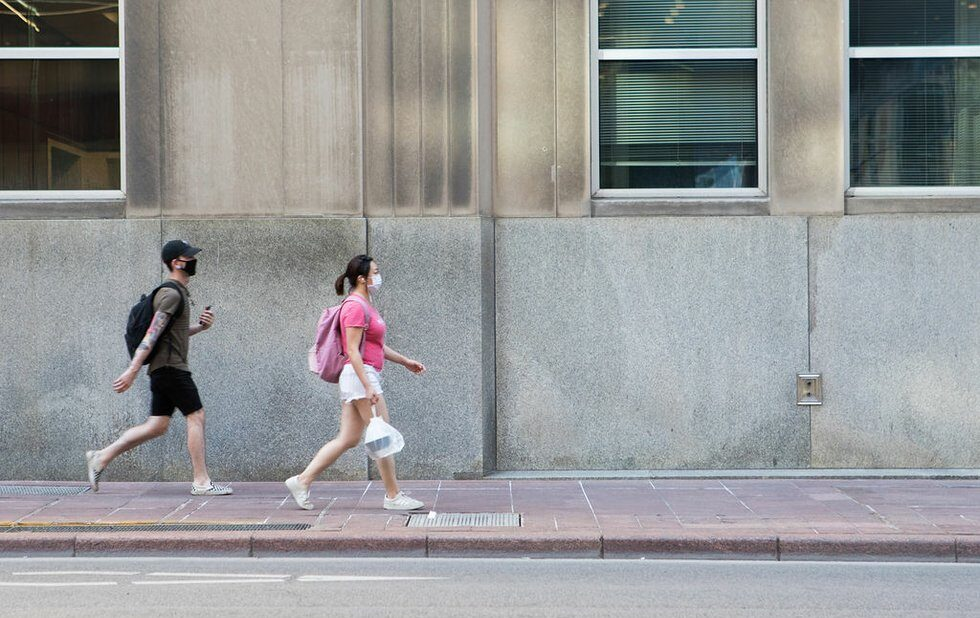A photo of two people walking through Toronto in face masks during the coronavirus pandemic on July 3, 2020