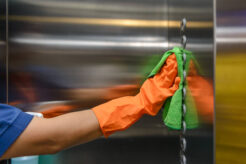 A cleaner wipes an elevator wall in an apartment building.