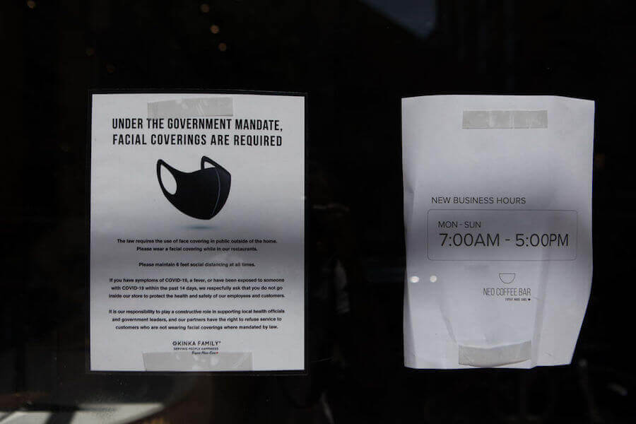 A photo of a store sign informing people to wear face masks to curb spread of COVID-19
