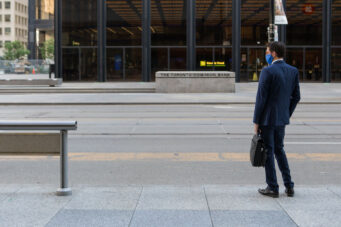 """alt=""""man wearing a face mask waiting for TTC streetcar in Toronto's financial district"""""""