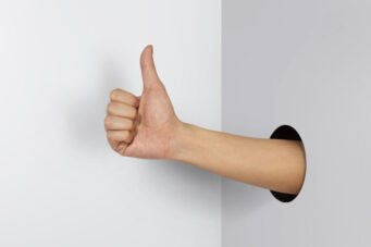 Hand giving a thumbs up through a whole in the wall.