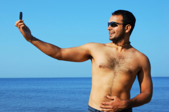 A man takes a shirtless selfie on the beach.