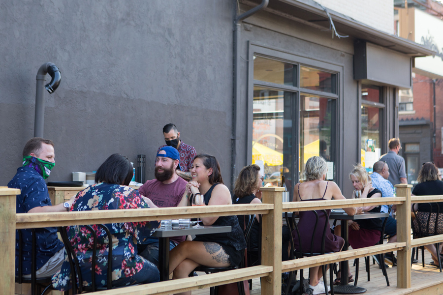 People sit on a restaurant patio in Toronto in July 2020.