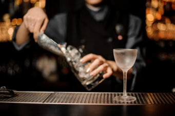 A bartender adds ice to a glass.