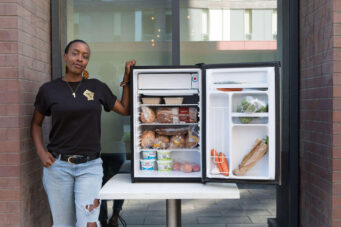 A photo of Allison Gibson with a community fridge at Paintbox Catering and Bistro.