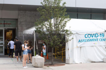 A photo of people waiting outside a COVID-19 assessment centre in Toronto, Ontario