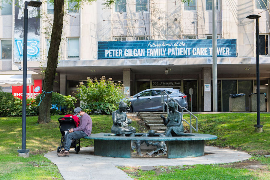 A photo of a man sitting outside Sick Kids hospital in Toronto