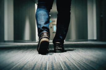 A photo of a person walking down a hallway