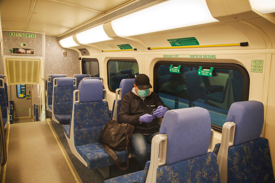 A photo of a man in a face masking riding the GO Train in Toronto.