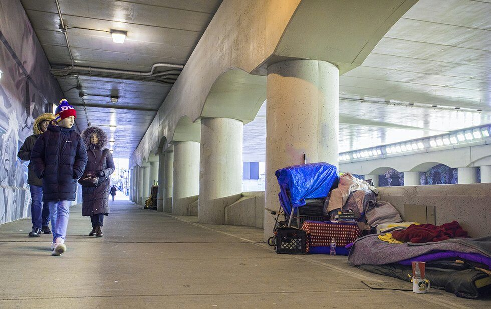 A photo of people walking past a homeless encampment near Union Station in Toronto in winter 2020.