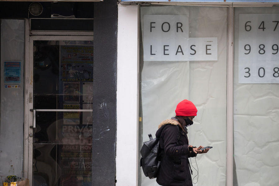 A photo of a person in a mask walking by an empty storefront in Toronto in October 2020