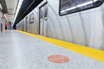 A photo of a social distancing sign in a TTC subway station