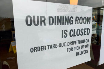 A photo of a takeout and delivery sign in a restaurant window