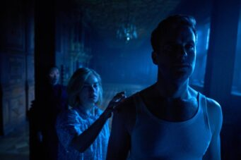 Kristin Scott Thomas, Lily James and Armie Hammer stand in darkness in Netflix's Rebecca.
