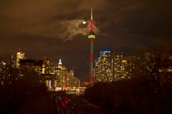 A photo of the CN Tower at night lit up with Christmas lights