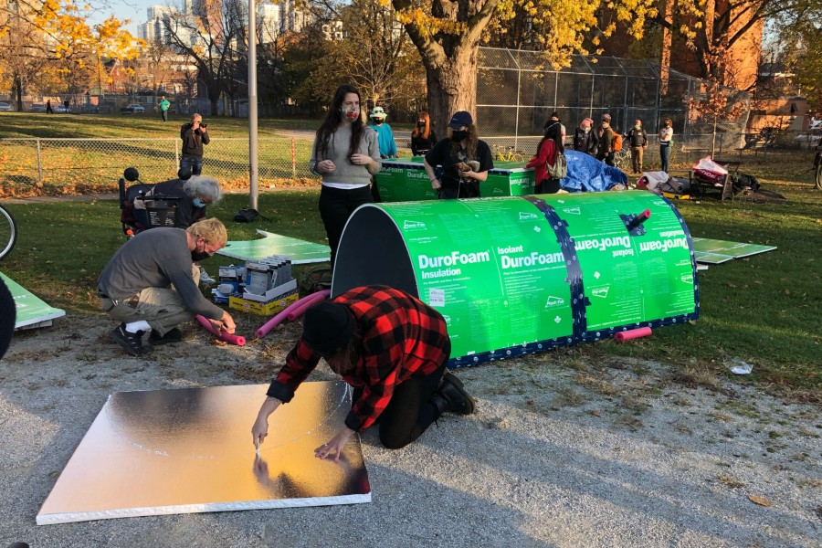 A photo of people building temporary housing structures in Toronto for people sleeping outside.