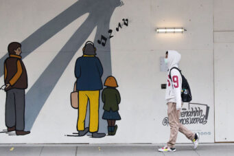 A person in a face mask walks by street art in Toronto during the COVID-19 pandemic on November 27, 2020.