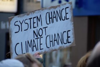 A photo of a sign that says system change not climate change