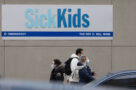 A photo of people walking past SickKids hospital in Toronto