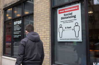 A person walks past a COVID-19 social distancing sign in Toronto