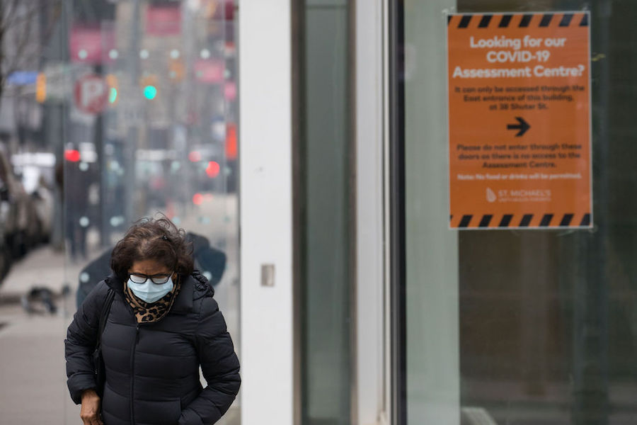A photo of a person in a face mask walking past a COVID-19 testing centre in Toronto on January 15, 2021