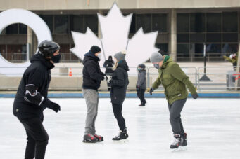 A photo of people skating at Nathan Phillips Square in Toronto