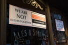 A sign in a small business says We Are Not In This Together