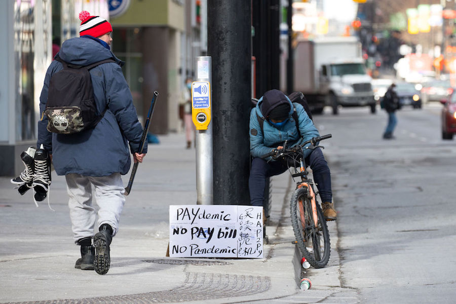 A photo of a person with a paydemic sign in Toronto on January 22, 2021