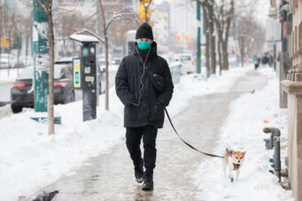 A photo of a person walking a dog in Toronto during COVID-19 pandemic on February 22 2021
