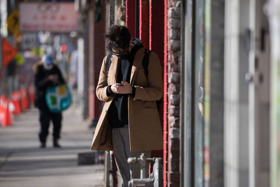 A photo of a person on their cellphone during COVID-19 pandemic in Toronto on January 22, 2021