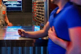 A photo of a person at a reception desk at a bathouse