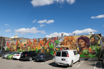 A photo of the Reggae Lane music mural in Toronto's Little Jamaica neighbourhood with cars parked in front