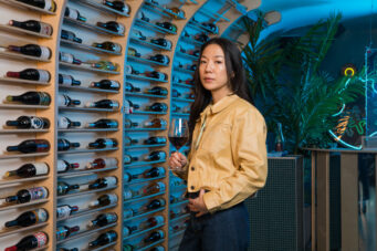A photo of Grape Crush co-owner Nancy Chen beside a wall of bottles
