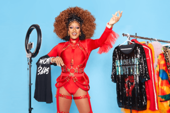 A photo of drag queen Tynomi Banks dressed in red posing in a studio next to a clothing rack