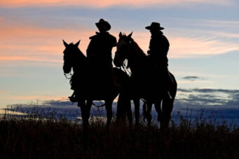 A photo of two cowboys on horseback in silhouette at sunset