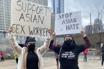 Vixen Vu holds up a placard at the #StopAsianHate rally demanding support for sex workers
