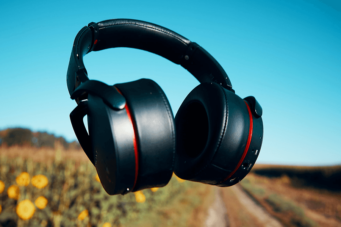 A photo of headphones floating in the air near a roadside