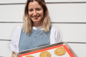 A photo of Lucy Kirby from Breadhead holding a tray of cookies