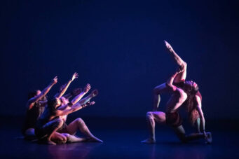 A photo of dancers on a minimal blue stage in the show Miigis