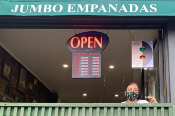 A photo of Jumbo Empanadas owner Irene Morales with a mask on in the window of her restaurant