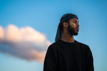 A photo of Toronto singer/songwriter Mustafa against a blue sky and clouds
