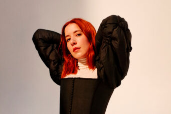 A photo of Katie Stelmanis of Austra with bright red hair