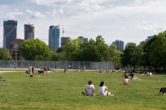 A photo of people hanging out on the grass in Trinity Bellwoods Park in Toronto