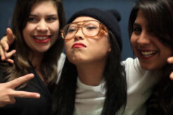 A photo of Awkwafina posting for a photo with two people in Bad Rap