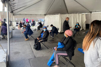 A photo of people sitting in a vaccine clinic in East Toronto after receiving doses
