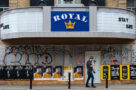 A person walks past the Royal Cinema in Toronto, which is boarded up